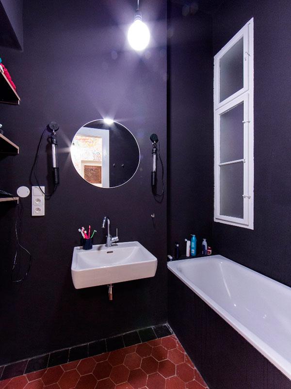 Koupelna s původní dekorovanou dlažbou. Koupelnu i toaletu koncipovali designéři z 0,5 Studia kontrastně ve vztahu k ostatním místnostem bytu. Foto: Peter Fabo