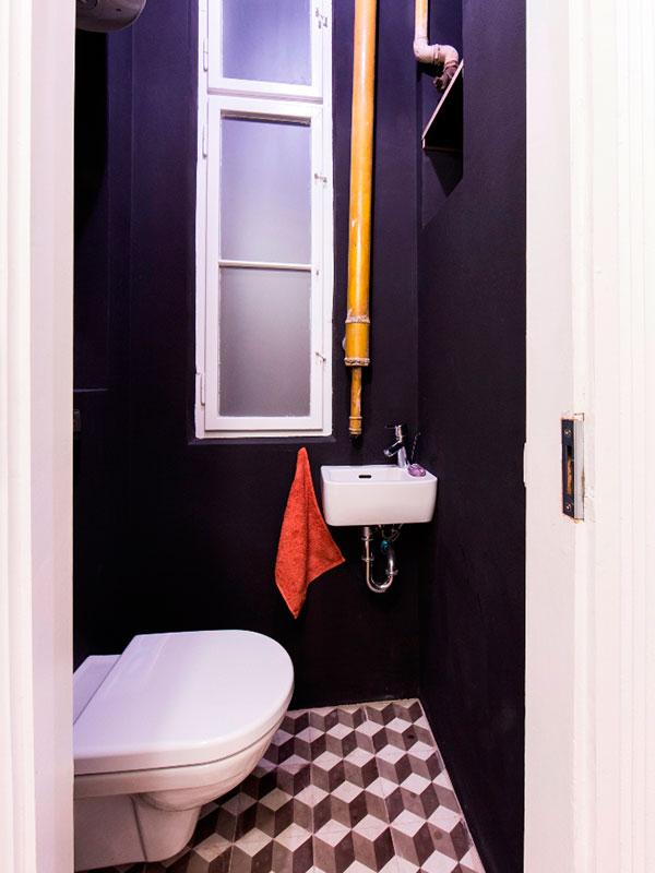 Černá toaleta s přiznanými technickými prvky. Stejně jako koupelna má okno do světlíku s výplní ze satinovaného skla. Foto: Peter Fabo