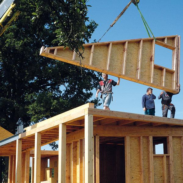 """Celá konstrukce domku je ze dřeva. Velká část prvků byla prefabrikovaná, na stavbě se pak jen usazovaly do sloupkové konstrukce. Usazování štítů se neobešlo bez zmatků. """"Chlapi, máte to obráceně,"""" volal jeřábník, když usazovali přední štít převráceně, podle návrhu. Foto Veronika Nehasilová"""