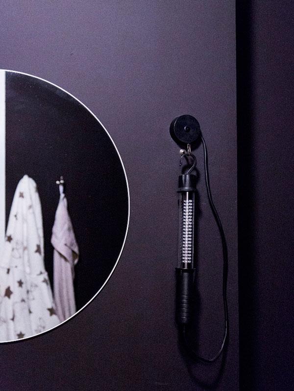 Detail osvětlení v koupelně. Povrchy tu tvoří černý fasádní nátěr. Foto: Peter Fabo