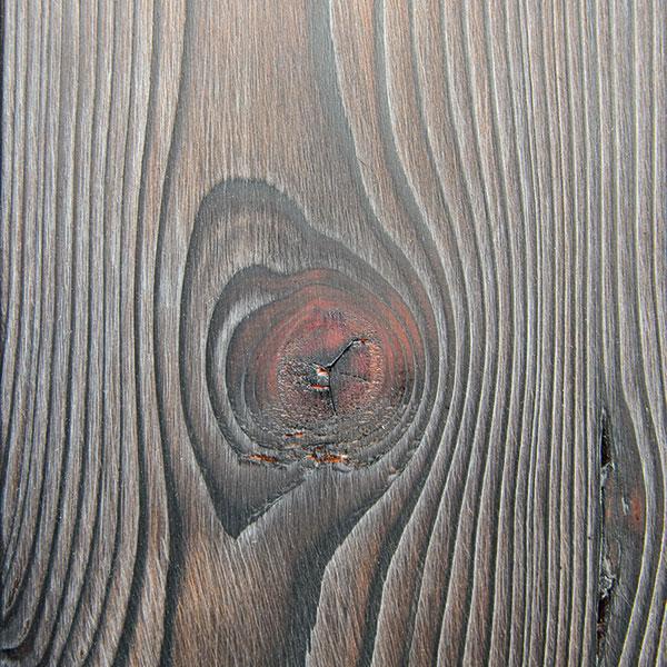 Působivý efekt na fasádě je dán několikastupňovou povrchovou úpravou. Nejprve tesaři fasádní profily opálili, vykartáčovali, následně se nanesla vrstva bílé olejové lazury, která se po zavadnutí vytírala bavlněným hadrem. Výsledkem je trojí barevnost zdůrazňující kresbu dřeva. Foto Veronika Nehasilová