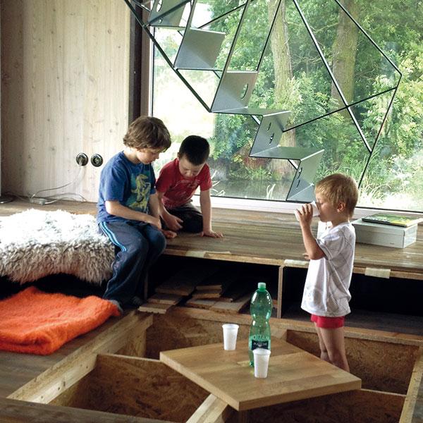 Ráj pro děti. Snedostatkem úložných prostor si architektka poradila chytře. Vytvořila je vdutinách pódií, které se zavírají pomocí dřevěných poklopů. Než se zaplní věcmi, udělají radost zejména synovi majitelů ajeho kamarádům. Umíte si představit lepší místo na hraní? Foto Veronika Nehasilová