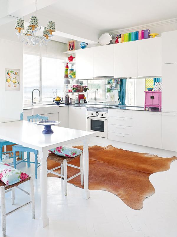 Bílá magie. Aby byt působil světlejším aprostornějším dojmem, nejen stěny apodlaha, ale istůl, kuchyňské skříňky aspotřebiče jsou bílé. Foto AM / Photoforpress