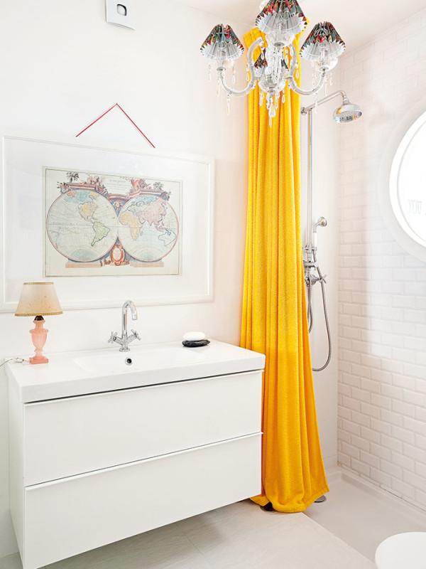 Stylová jednotnost. Bílý základ místnosti, výrazný žlutý sprchový závěs alustr, které ladí sdekoračními prvky vsousedním obýváku, sjednotily oba prostory. Foto AM / Photoforpress