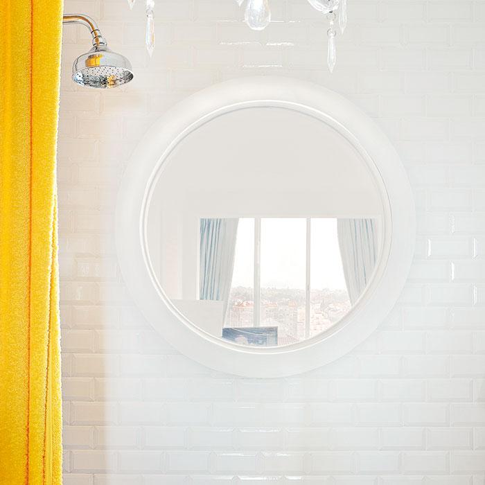Originální spojení. Designéři vymysleli izpůsob, jak prosvětlit aozvláštnit koupelnu na konci vstupní chodby – lodní okno vesprchovém koutě. Při sprchování tak máte výhled do obýváku. Foto AM / Photoforpress