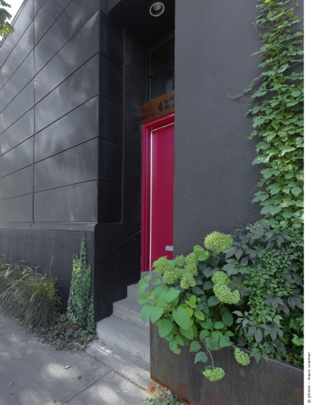 """Vchod do domu, na jehož střeše vytvořila šikovná architektka působivý """"byt"""" na čerstvém vzduchu. Černá plocha fasády se ve střešním prostoru záměrně opakuje."""