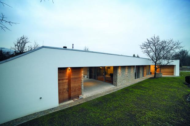 Dřevěnou část tvoří dvoje dveře. Levé skrývají sociální zařízení pro venkovní terasu a pravé sklad posuvné stěny. Následuje kamenná stěna obývacího pokoje a okna do kuchyně.