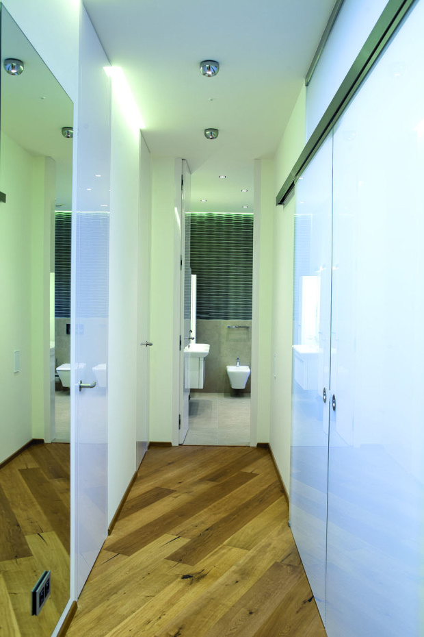 Chodbě do křídla majitelů a dcerky dominují průsvitné skleněné dveře. Dvoje pokojové vlevo, šatní posuvné vpravo. Rovně je společná toaleta s koupelnou.