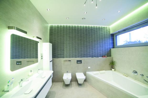 Keramický 3D obklad vytváří zvláštní prostorovou strukturu. Koupelna díky architektům zcela využila každý centimetr své plochy, bonusem je vana pod oknem. Osvětlení je stejně jako v celém domě ledkové, různého tvaru a ladění.