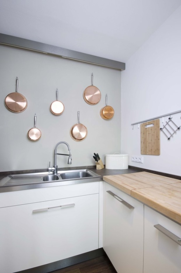 Stříbrné akcenty se vyskytují v celém bytě, například v podobě kulatých svítidel. Jen kuchyni dominuje měděná v podobě kvalitního měděného nádobí, které je jako chlouba vystaveno zavěšené na stěně nad kuchyňskou linkou.