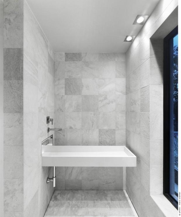"""Jednolité plochy křemene a mramoru spolu s podmítkovými bateriemi a """"vznášejícím se"""" umyvadlem koupelnu opticky odlehčují."""