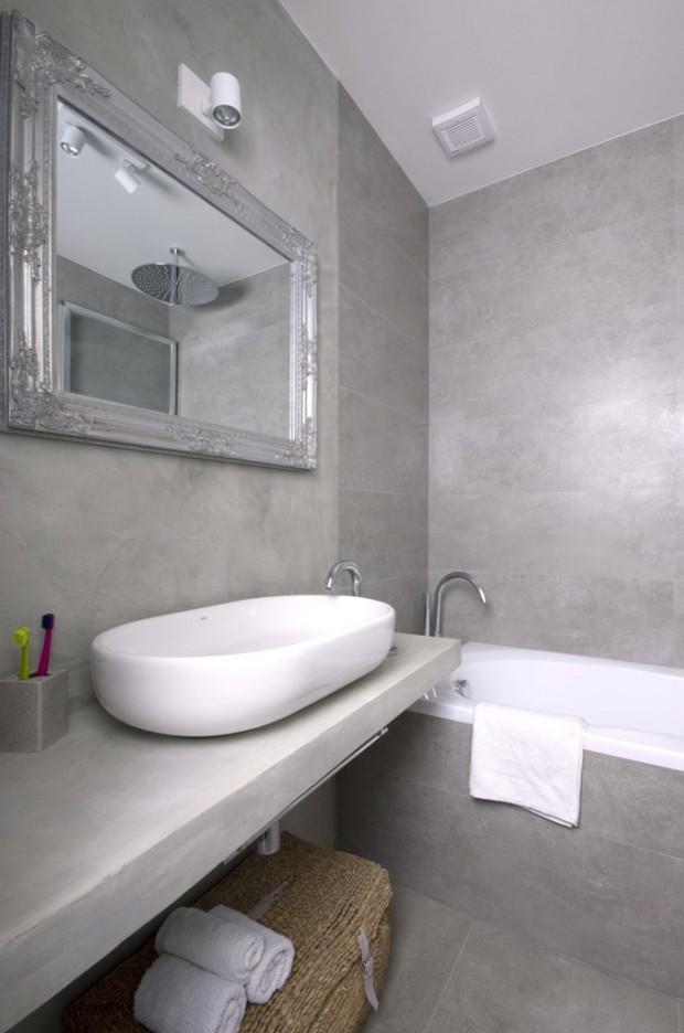 """Dekorativní zrcadlo se stříbrným rámem, zavěšené nad oválným umyvadlem """"na desku"""" ozvláštňuje interiér koupelny."""