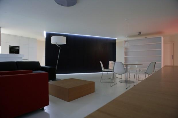 Denní prostor s pohovkami a jídelním stolem na pozadí multifunkčního kvádru. Povrch podlahy tvoří snadno udržovatelné linoleum, zvolené pro svou schopnost sjednocovat interiér.