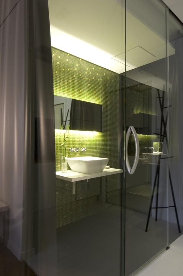 """Koupelna v luxusních temných tónech """"zahalená"""" leskem skel, ve kterých se odráží život v bytě, je stěžejním prvkem celé garsonky."""