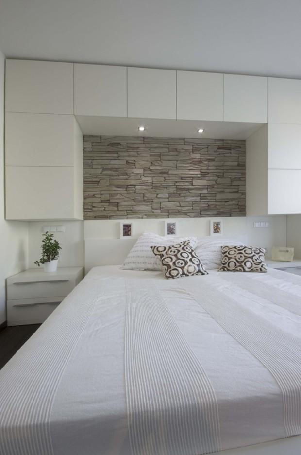 Světlá ložnice s barevností tón v tónu. Kamenný obklad nad postelí je možné večer nasvítit a vytvořit tak intimní atmosféru.