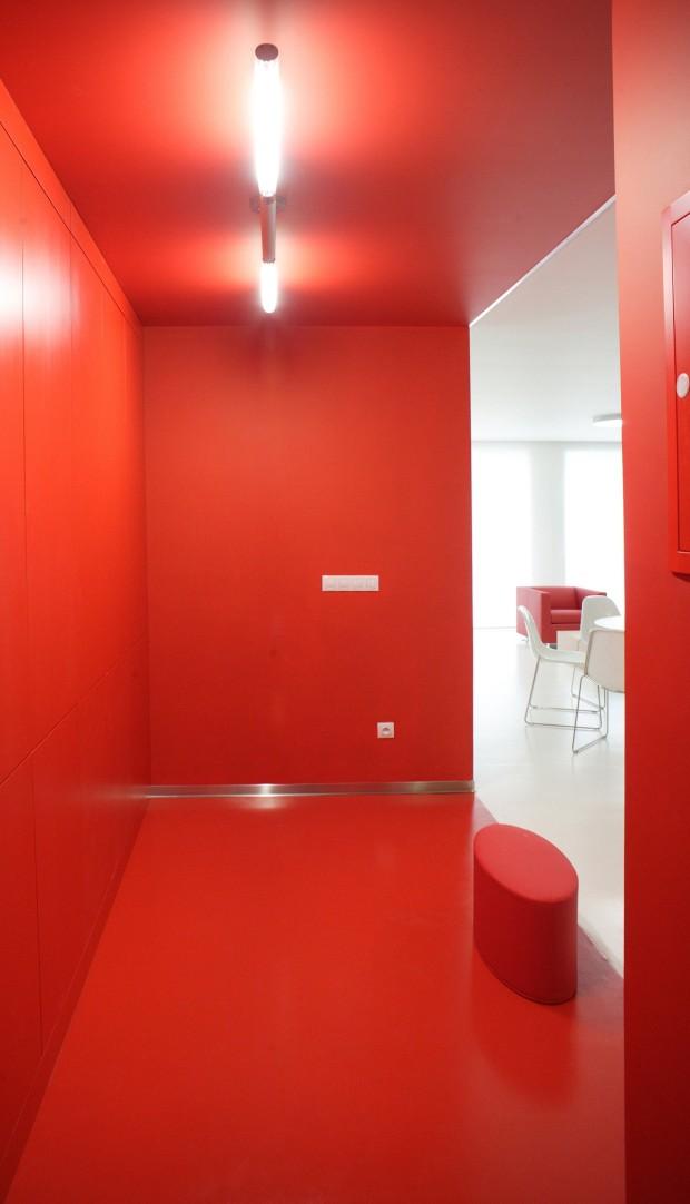 Červené zádveří s šatními skříněmi a oválným sedátkem na rozhraní červené a bílé působí jako bonbónek.