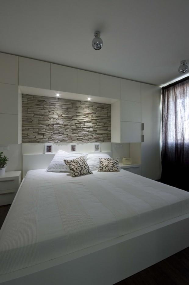 Nasvícený kamenný obklad nad postelí je při otevřených posuvných dveřích vidět od jídelního stolu, což večer vytváří příjemnou večerní náladu.