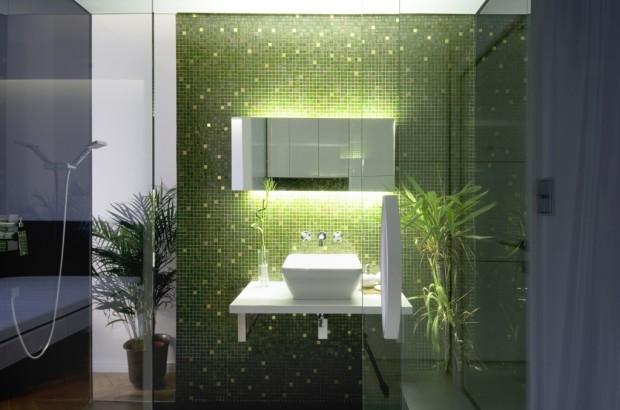 Třpytivá zelenozlatá mozaika s nasvíceným zrcadlem. Malý prostor za koupelnou funguje jako výklenek na exotickou rostlinu, která vytváří dojem pralesa.