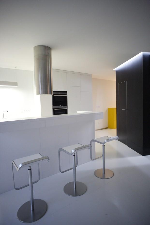 Kuchyňská linka v bílé barvě s barovým pultem. Černý kvádr v sobě v této části skrývá praktickou spíž.