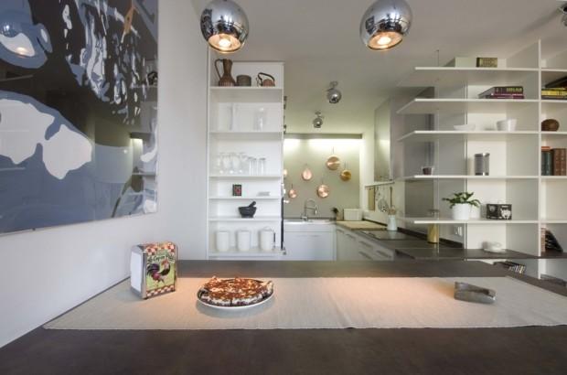 Jídelní stůl v barové výšce a pohled do kuchyně na zajímavou kompozici měděného nádobí.