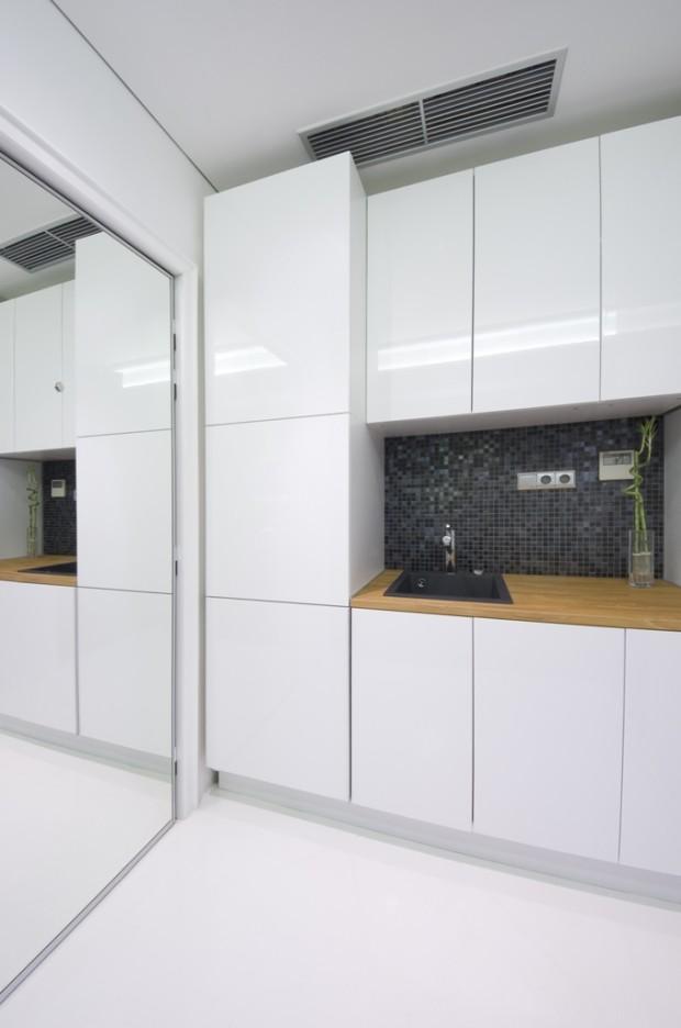 Jednoduchá bílá kuchyňská linka majiteli vyhovuje. Na stěně mezi skříňkami použil stejnou černošedou mozaiku jako na vnější straně koupelnového boxu.