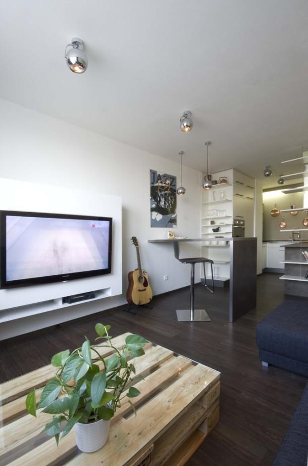 Obývací prostor s televizí začleněnou do bílé skříně upevněné na zdi. Konferenční stolek je vyroben ze dřevěných palet překrytých skleněnou deskou.