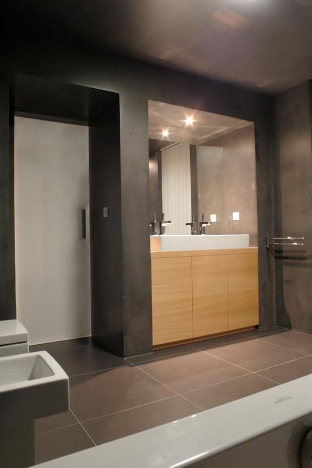 V koupelně je kladen důraz na jednotu celku se zdůrazněním jednoho detailu, kterým je zde pult se skříňkami pod umyvadlem ve světlém dřevě.