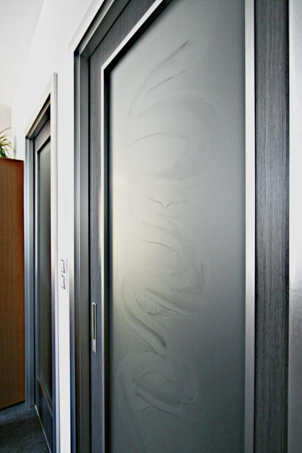 Pískované celoskleněné dveře po špatné údržbě s viditelnými ušpiněnými plochami