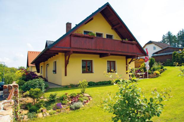Štít s přesahující střechou vytváří rámec pro příjemný balkón u rodičovské ložnice, ze kterého je výhled na pečlivě udržovanou zahradu.