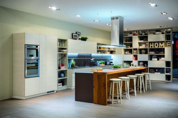 Čisté hladké plochy rozbíjejí otevřené police, které kuchyni dodávají dojem zabydlenosti. Dřevěný pult odkazuje k aktuálnímu trendu přírodních materiálů.