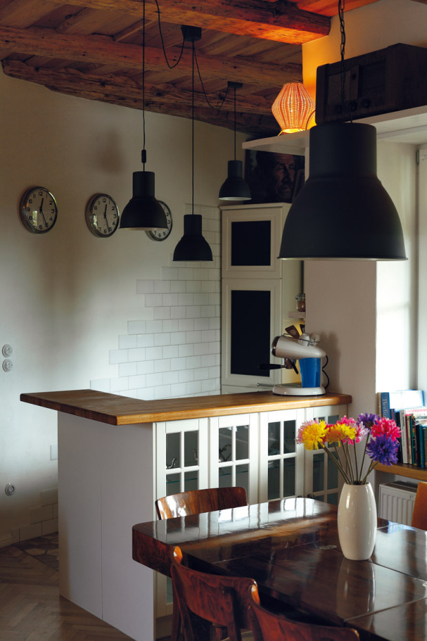 Motiv obnažené cihlové zdi z obývací části se opakuje i v kuchyni, v kombinaci s bílou linkou a doplňky působí romanticky.