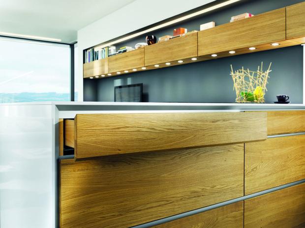 Minimalismus. Stále více výrobců volí absolutně hladký, ničím nerušený povrch kuchyňského nábytku. Madla a úchytky tak stále častěji nahrazují speciálně upravené, zkosené hrany zásuvek a další důmyslné systémy: Push to Open, elektrické otevírání…