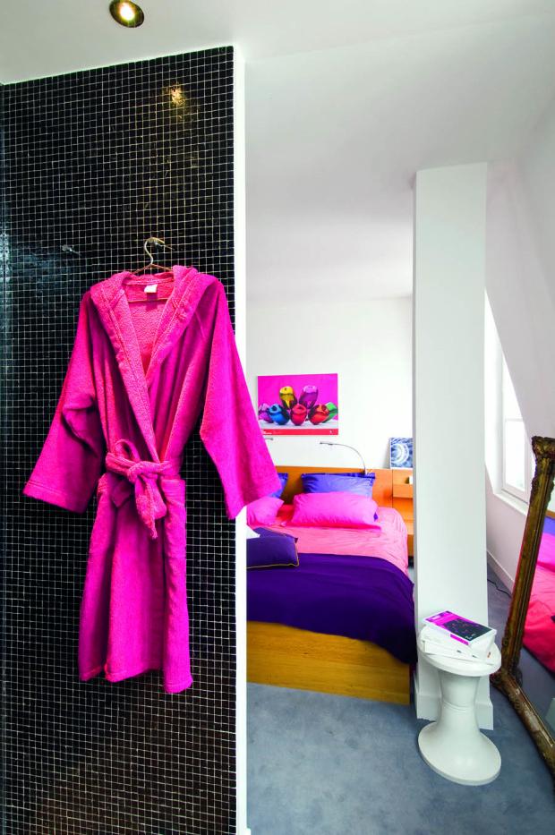 Ložnici a koupelnu odděluje jen krátká příčka. Barevně neutrální základ, který vytvořily bílé, šedé a černé plochy podlah a stěn, oživují hlavně jasně růžové textilie a doplňky.
