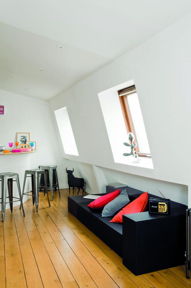 Jednoduchou černou pohovku oživují barevné polštáře, které slibují pohodlí a pobízejí hosty k odchodu z kuchyně.