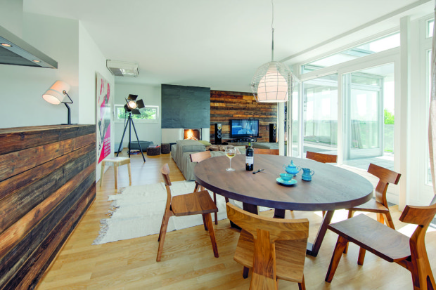 Masivní židle Fin Chairs z ořechového dřeva od anglické firmy Matthew Hilton materiálově ladí s obkladem a díky jednoduchým čistým liniím šaramantně zapadly do tohoto ležérně elegantního prostoru. Krb je pozůstatkem původní výbavy bytu.
