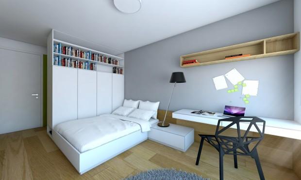 Široká postel je umístěná za šatníkovými skříněmi, jejichž zadní stěnu tvoří členěný obklad. Ten v jejich vrchní části vystřídá knihovna.