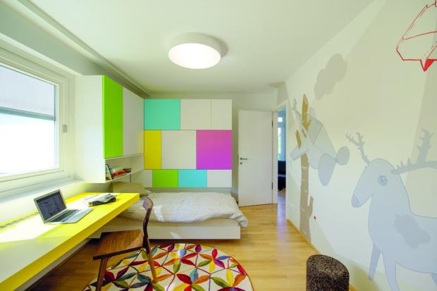 Zajímavé řešení šatníku v dětském pokoji vzniklo jednak kvůli limitující dispozici a jednak díky kreativitě architektů. Úložné prostory jsou sice přístupné jen z postele, to však u přechodného bydlení pro dítě není žádnou překážkou.