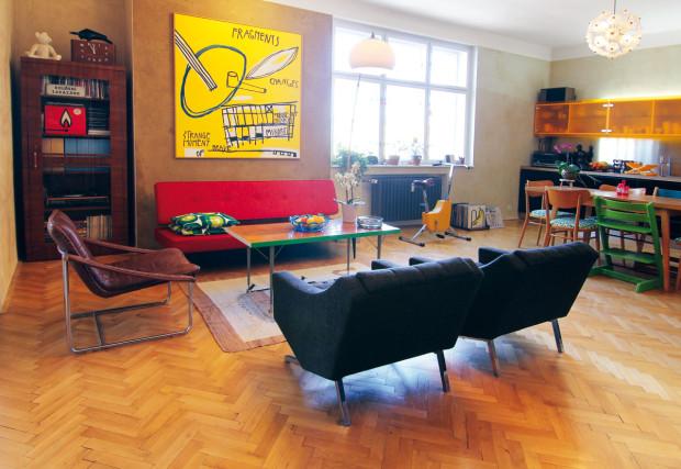Centrálnímu prostoru dominují výrazné barvy, typické pro ladění druhé poloviny minulého století. Původní dřevěné parkety a hnědá hliněná stěrka vytvářejí neutrální pozadí žlutému obrazu.