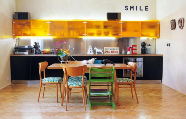 Současnost kuchyňské linky je designově a materiálově přiznána – vyrobili ji z betonářské překližky, která vyhovovala svými voděodolnými vlastnostmi. Díky satinovanému plastu podsvícenému zářivkami se horní řada skříněk stává působivým světelným zdrojem.