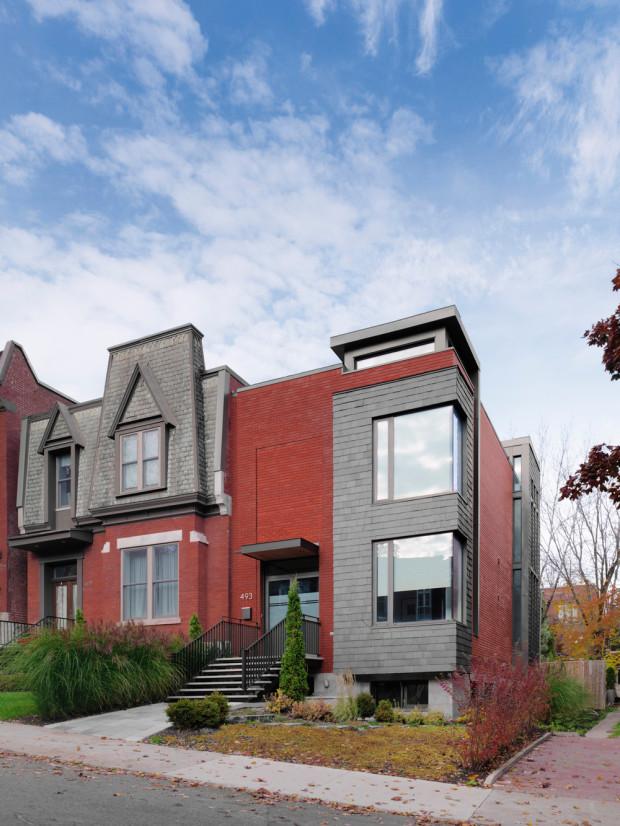 Rohový výklenek se dvěma okny oblékli architekti do stejného, tmavě šedého hávu z břidlice, jaký můžeme vidět i na sousedním domě. Stejně jako ostrý kontrast s oranžovorudou cihlovou fasádou.