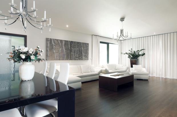 Prostorný obývák s kuchyní je orientován na západ, a tak nemá v nejvíce využívaných hodinách nouzi o slunce. Celý prostor je laděn do kontrastu prvků tmavého dřeva a bílé barvy čalounění a stěn.