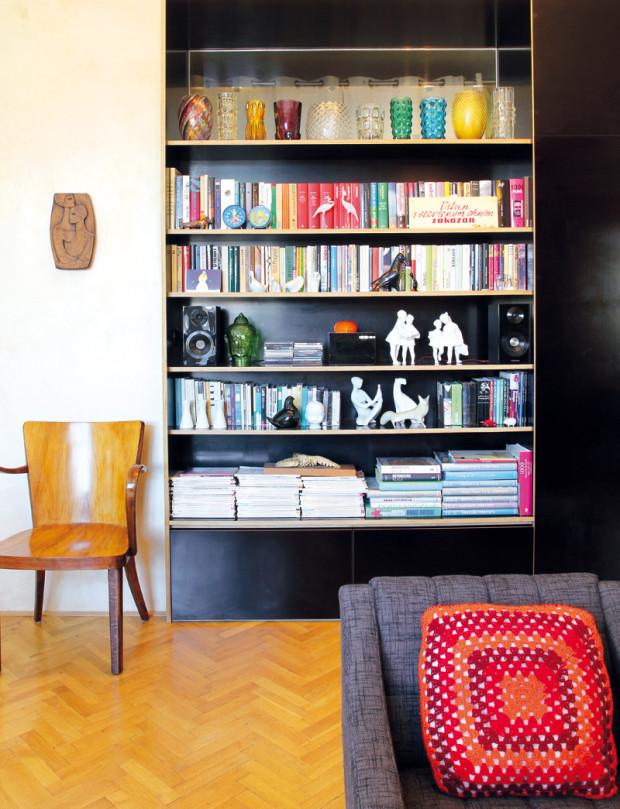 """Souvislá plocha, kterou vytváří na míru vyrobená knihovna zabudovaná do niky po původních dveřích a nové dveře vedoucí do vstupní haly, je jedním z přiznaných """"novotvarů"""" v bytě."""