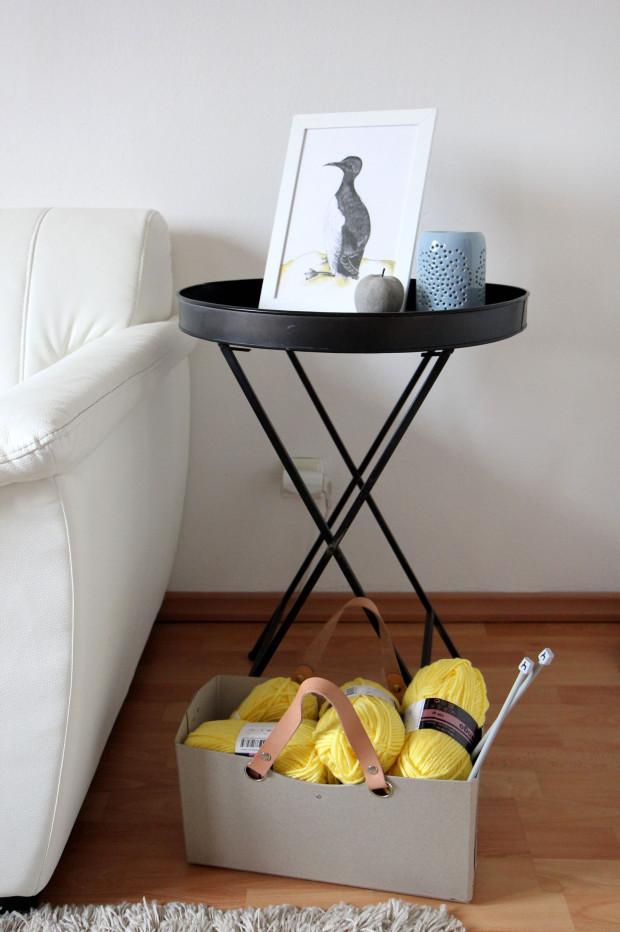 Osazenstvo vedle sedačky v obýváku se čas od času změní – od stolku až po dekorace. Když je bílé příliš moc, stolek z IKEY nahradí černý plechový od Broste a naopak. A kilo citrónů zamění lepenkový koš od značky Kazeta s pletací přízí.