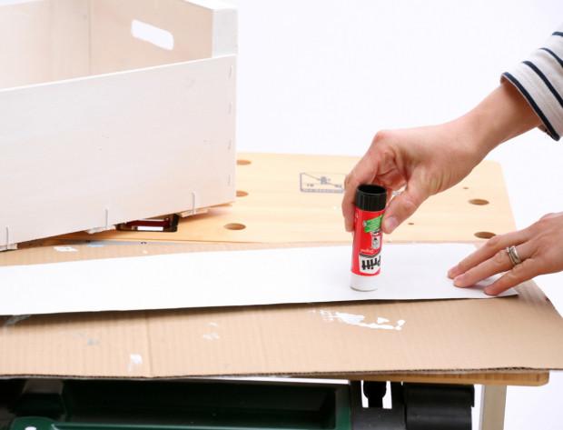 Z balicího papíru vystřihněte požadovaný tvar a naneste na něj tuhé lepidlo. (Pokud chcete, aby bednička sloužila na uskladňování hraček, volte papír s hravým motivem.) Nepoužívejte tekuté lepidlo, jelikož papír by se mohl zvlnit.