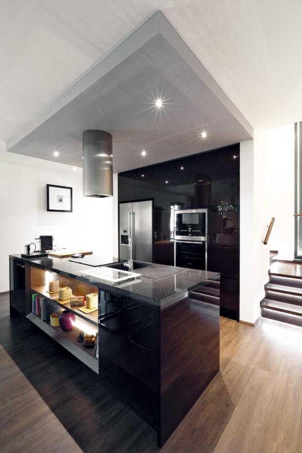Kuchyň navzdory propojení s obývací částí působí kompaktně díky sníženému sádrokartonovému stropu. Vysoké skříně využívají niku vytvořenou schodištěm.