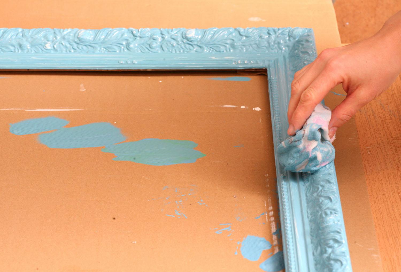 4 Když barva začne schnout (asi za 10 minut), rám jemně přetřete vlhkým hadříkem – tak na místech, kde je ornament vystouplý, setřete modrou barvu a odkryjete bílé plochy.