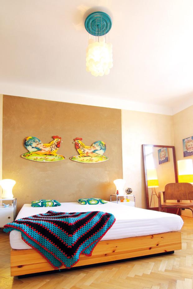 """Novou postel s """"čelem"""" tvořeným hliněnou omítkou doplňují dobové noční stolky a dřevěné zrcadlo. Ložnice jako pozůstatek původního obývacího pokoje."""