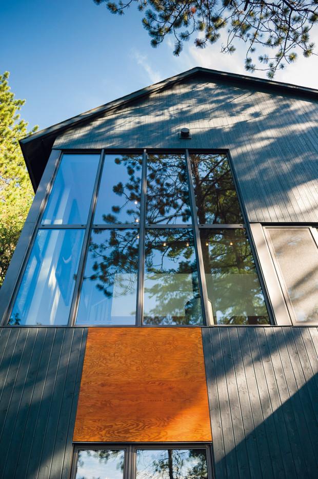 Hra s osami. Důraznost horizontálního směřování obkladu a oken zjemňují právě akcenty v podobě rezavé překližky, na níž je krásně vidět přirozená struktura dřeva.