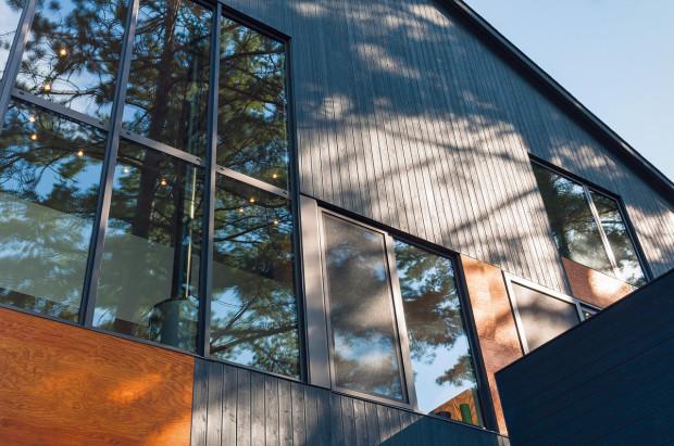 Fasádu tvoří celkem tři působivé prvky. Prvním je horizontální dřevěný obklad, druhým jsou výrazné vsadky z rezavé překližky a třetím velké prosklené plochy v šedých rámech.