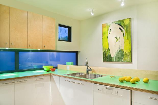 Přestože v domě bylo nutné šetřit každým metrem, dopřála architektka majitelům opravdu velkorysou kuchyňskou linku s velkou pracovní plochou a dostatkem úložných prostor.